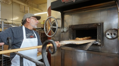 George DePasquale, Essential Baking Company Founder, pulling fresh barbari from the oven